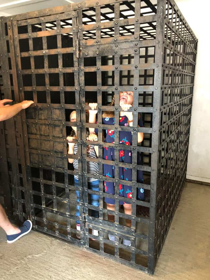 Children in an old-fashioned jail cell.