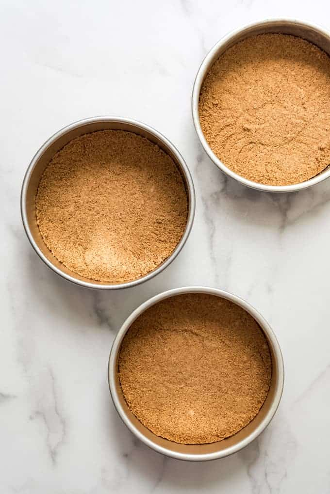 Three 8-inch round cake pans with graham cracker crust pressed into the bottom.