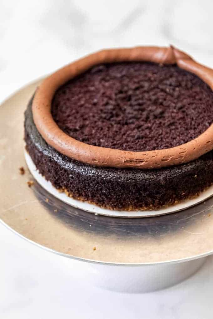 a chocolate cake with a rim of chocolate buttercream around the top