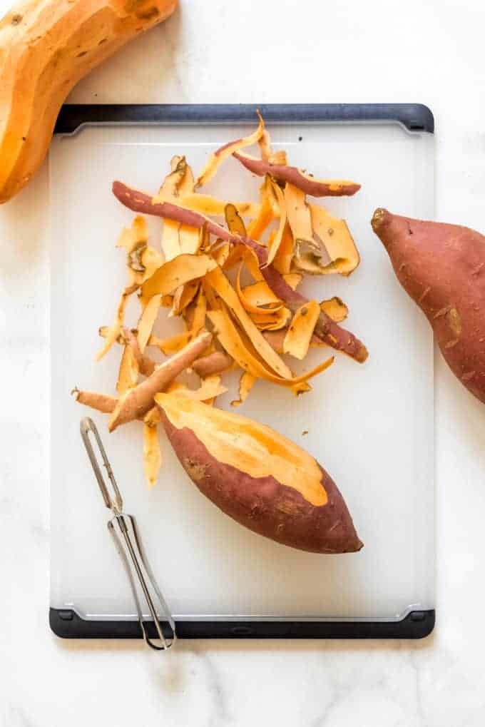 A sweet potato being peeled on a cutting board.