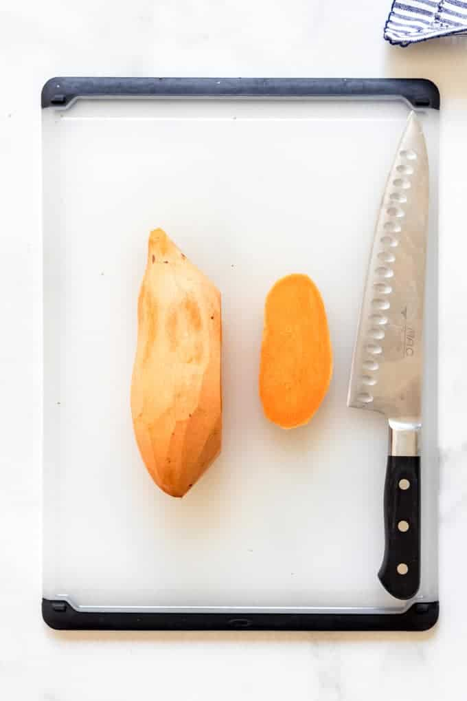 a sliced sweet potato on a white cutting board with a large knife