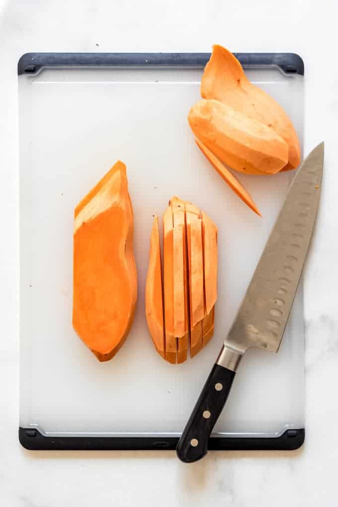 a knife and sliced sweet potatoes on a large cutting board