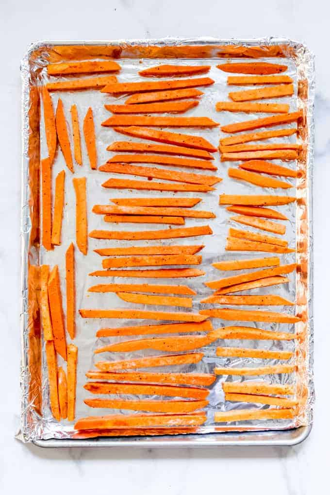 Individual sweet potato sticks arranged on a baking sheet.