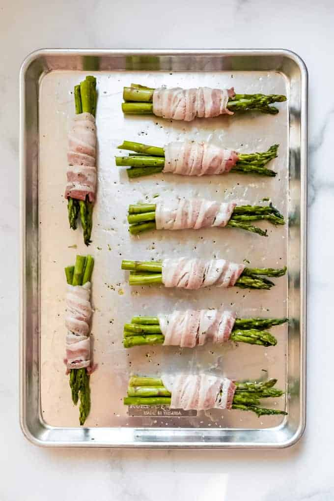 uncooked Bacon Wrapped Asparagus on silver baking tray
