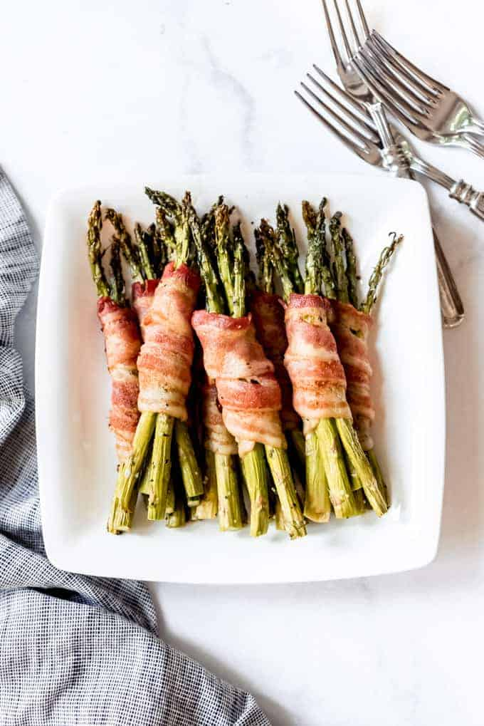overhead shot of asparagus wrapped in bacon on white plate with cloth and forks