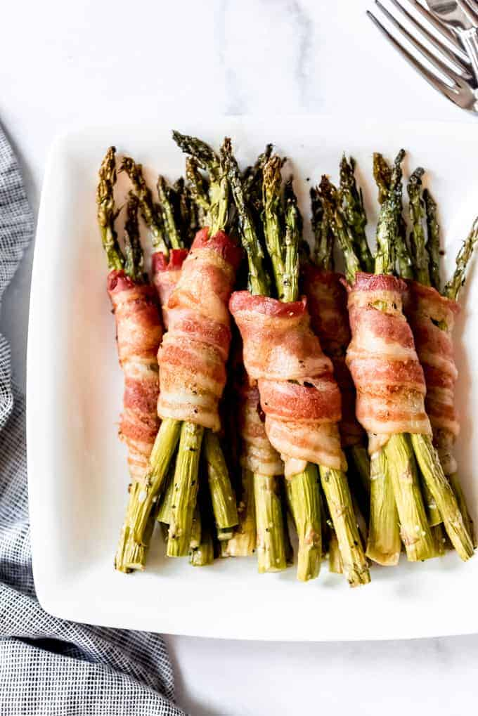 roasted asparagus with bacon on white plate