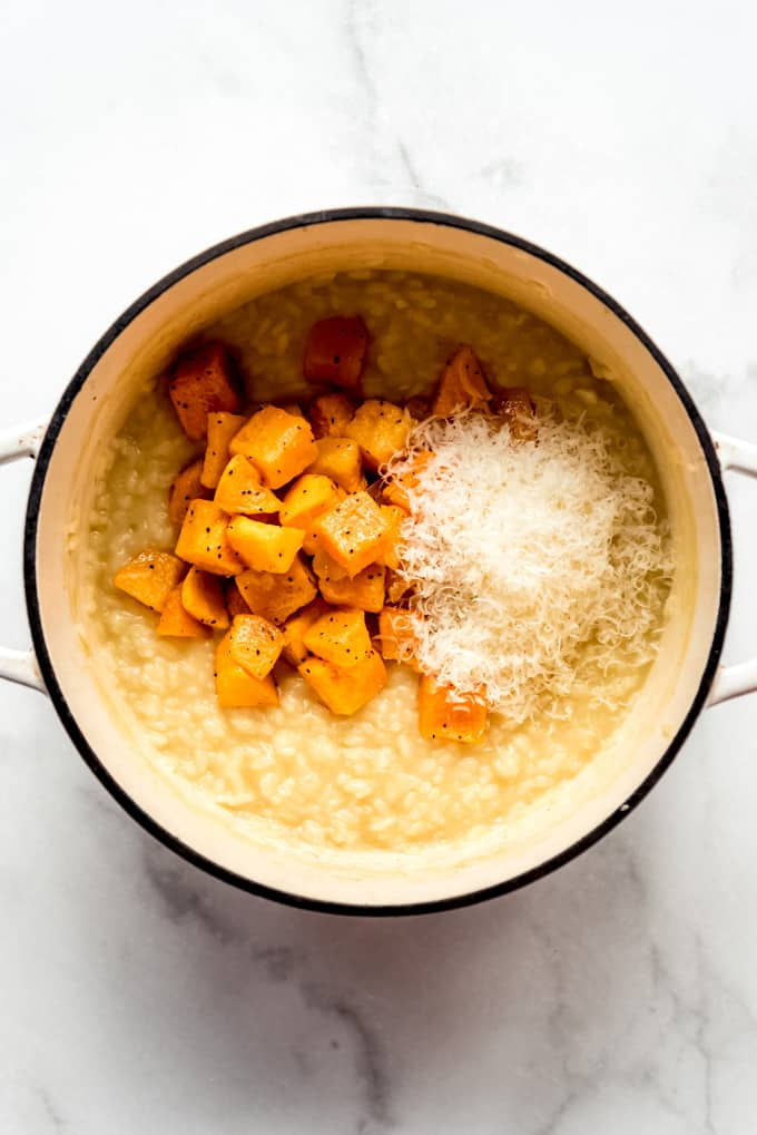A pot of risotto with roasted butternut squash and parmesan cheese.
