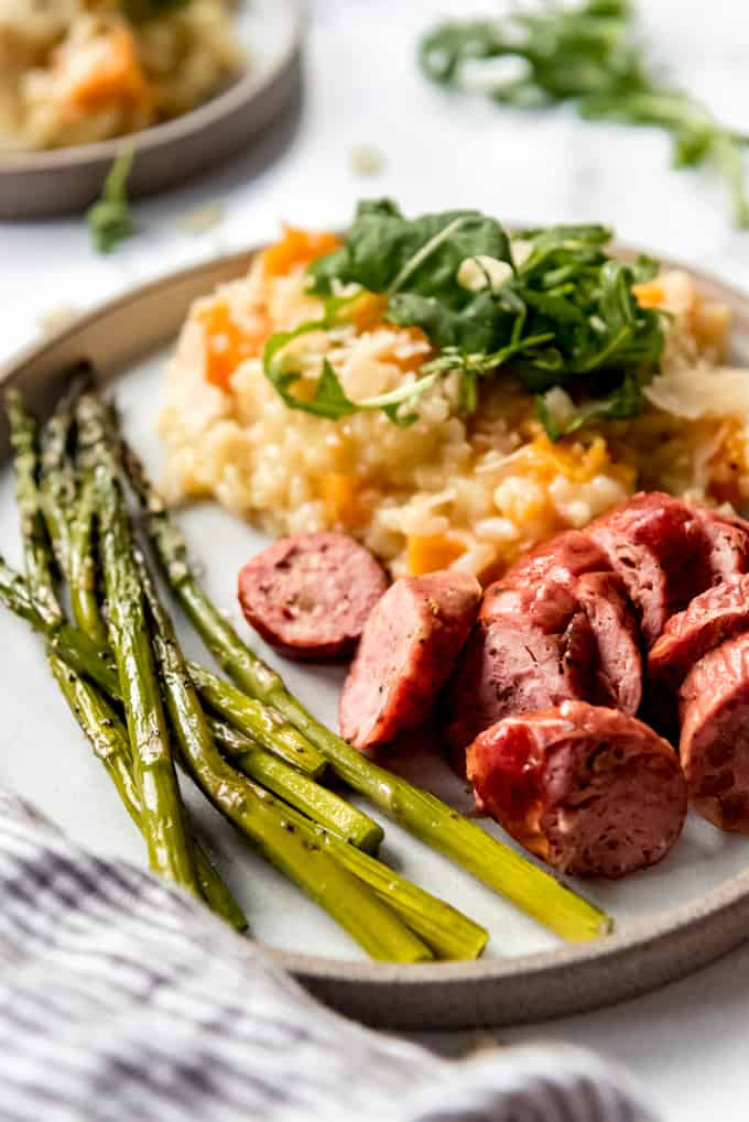 A plate of sausage, asparagus, and risotto.