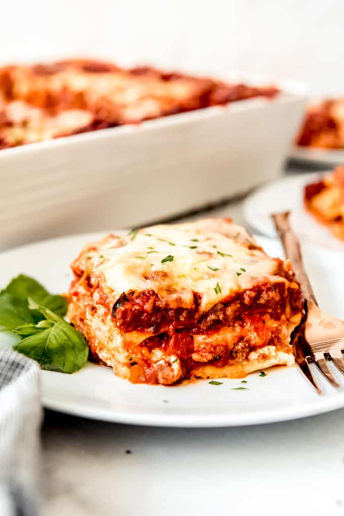 classic lasagna with fresh basil and parsley on white plate