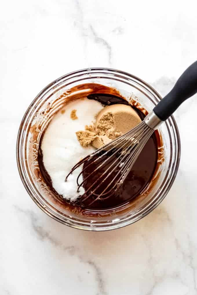 adding vanilla and sugars to the melted chocolate and butter with a whisk