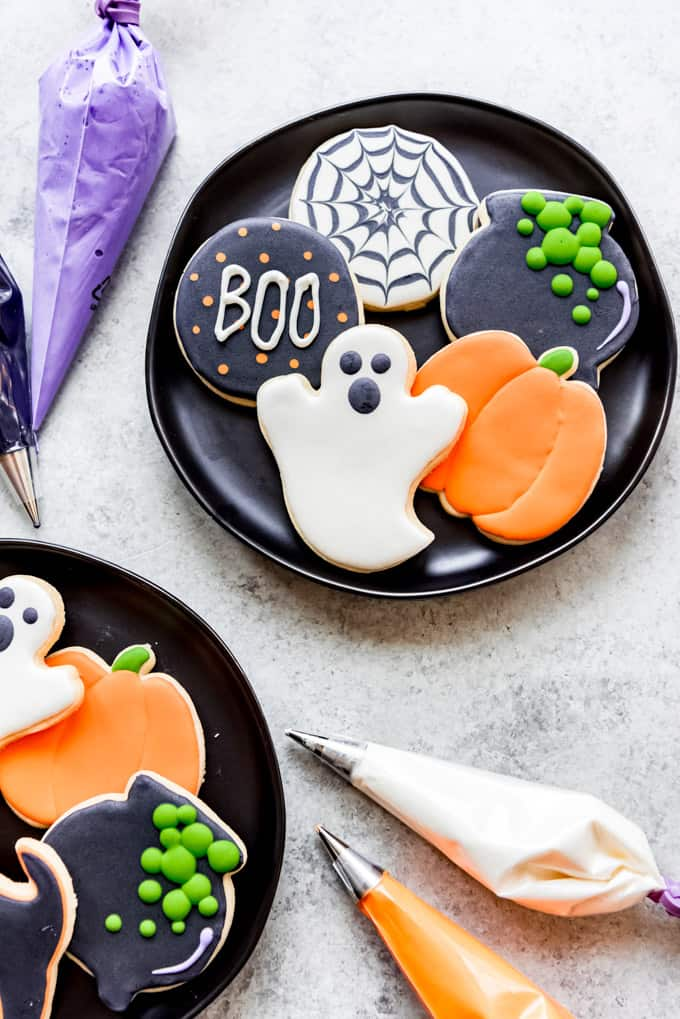 Black plates of decorated sugar cookies.