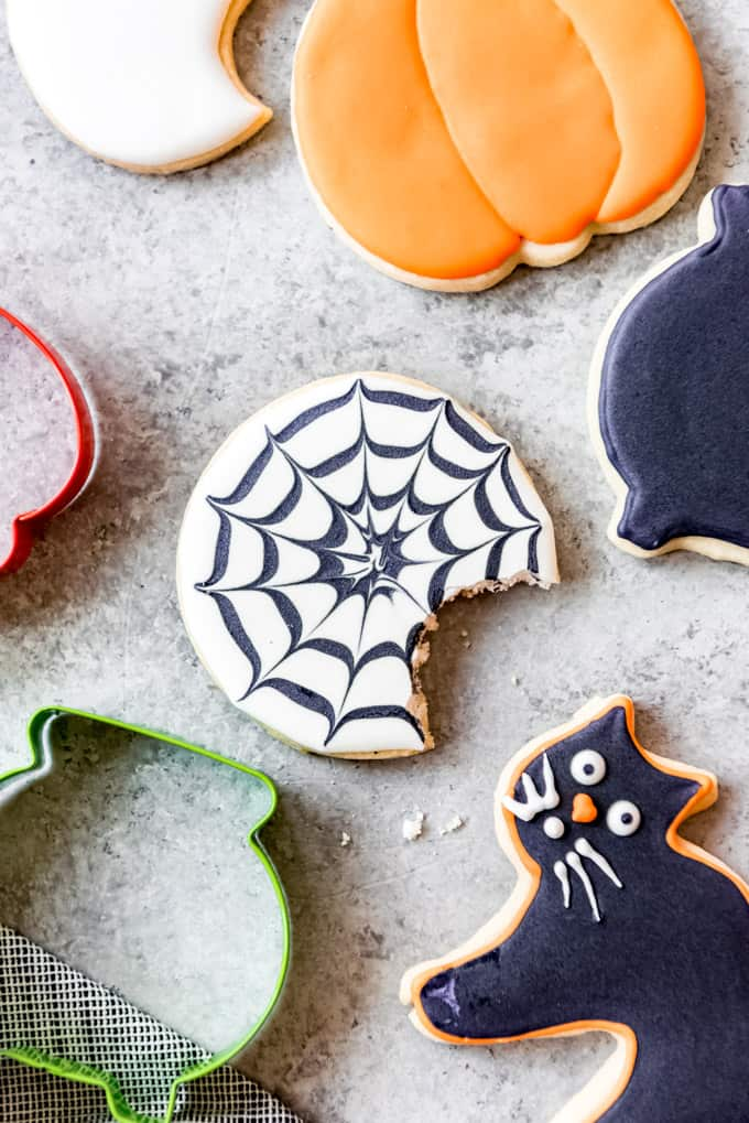 A spiderweb sugar cookie with a bite taken out of it.