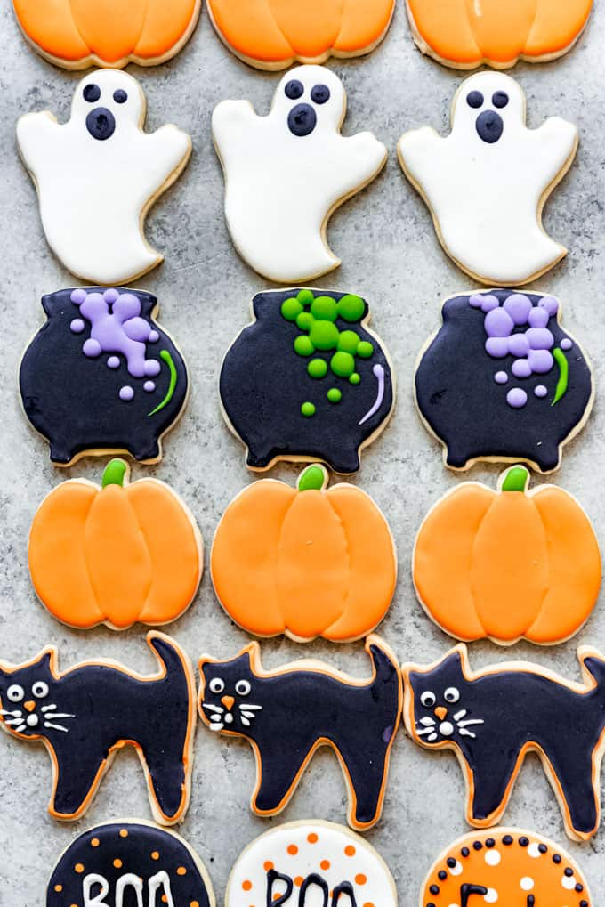 Rows of Halloween sugar cookies decorated like ghosts, cauldrons, pumpkins, and black cats.