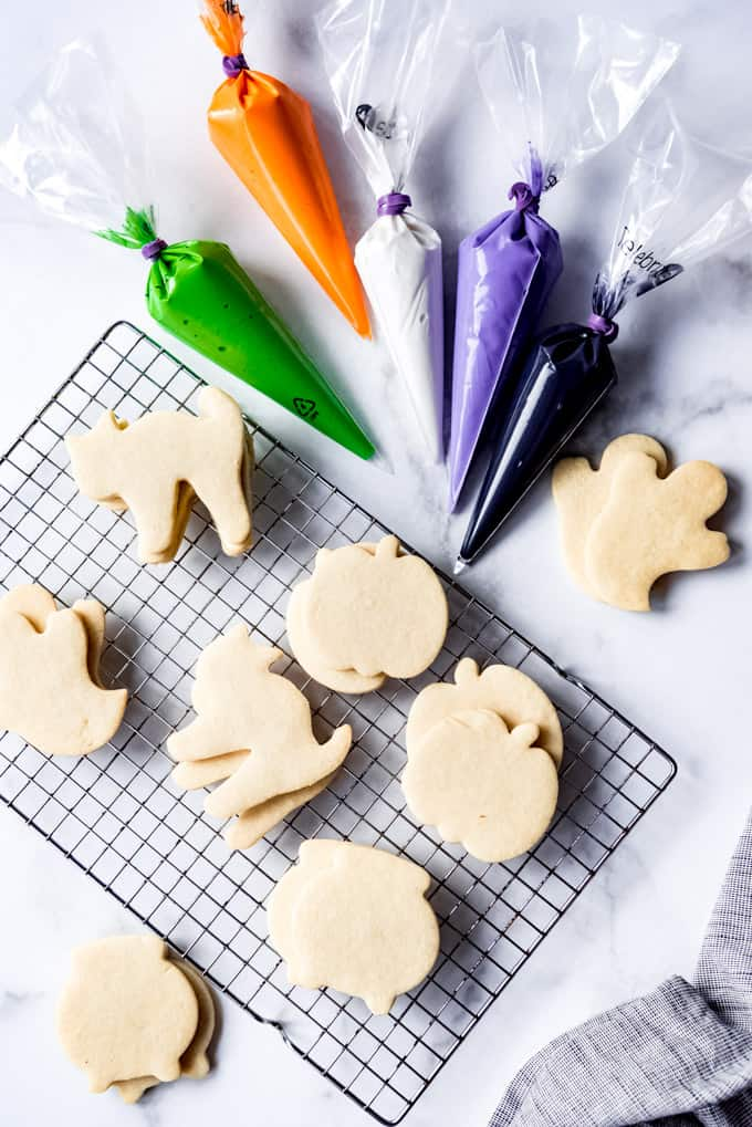 Undecorated sugar cookies next to bags of royal icing in Halloween colors.
