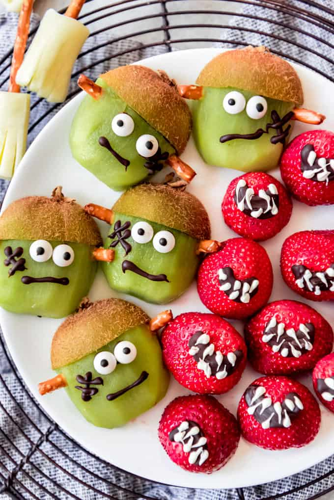 Kiwi decorated as frankenstein and strawberries decorated as mouths.