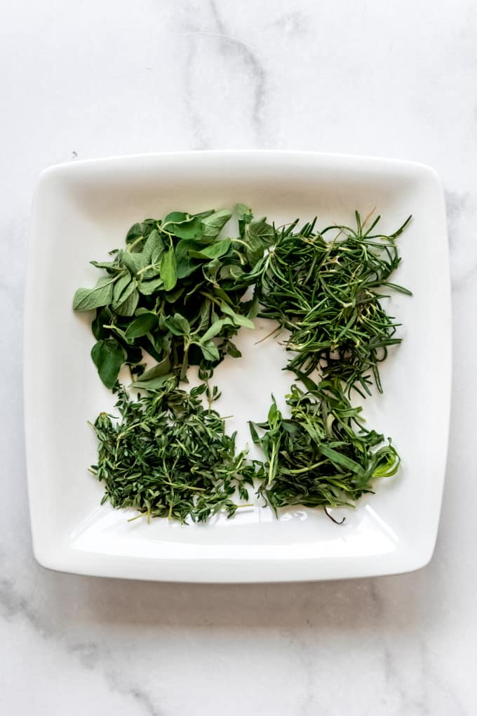 Fresh oregano, rosemary, tarragon, and thyme on a white plate.
