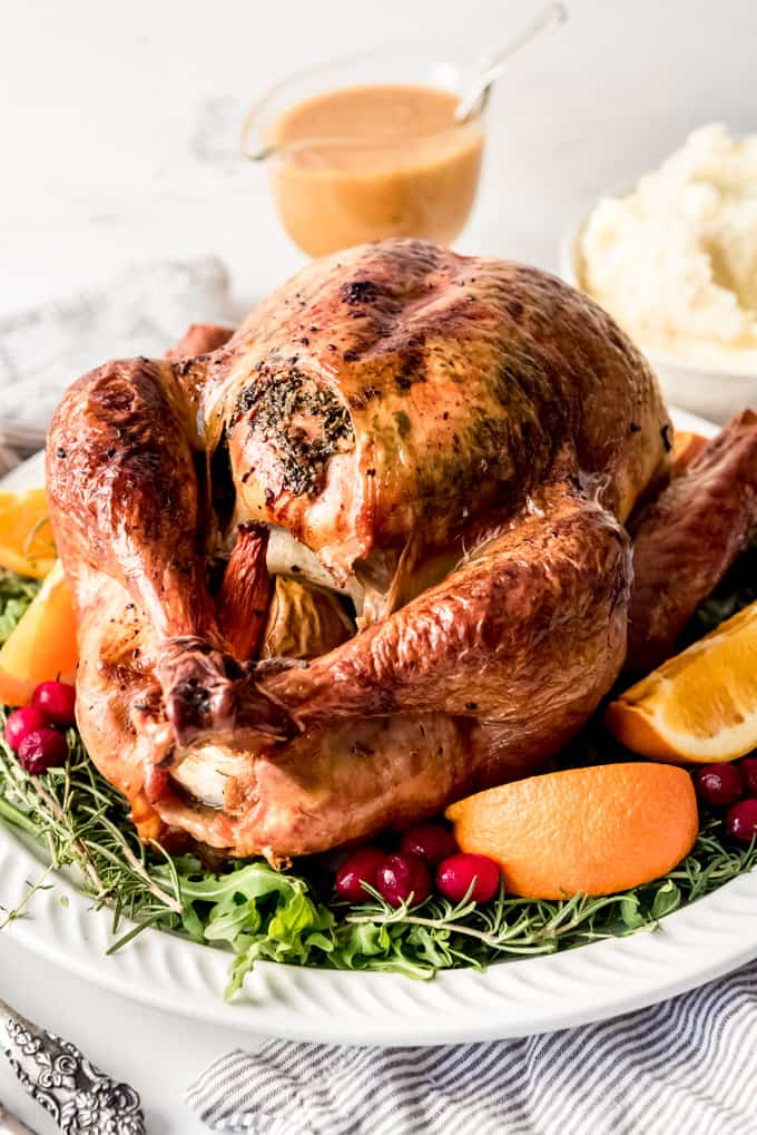 A roast Thanksgiving turkey on a platter garnished with fruit and herbs.