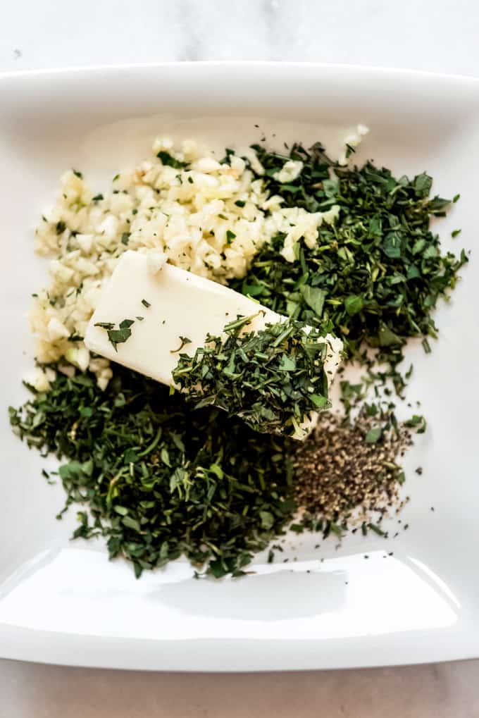 A stick of softened butter with chopped herbs and garlic on a plate.