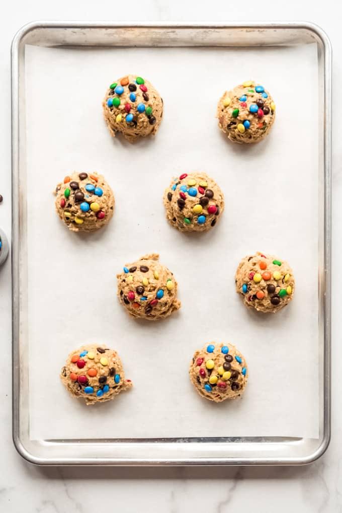 Eight balls of monster cookies dough on a baking sheet.