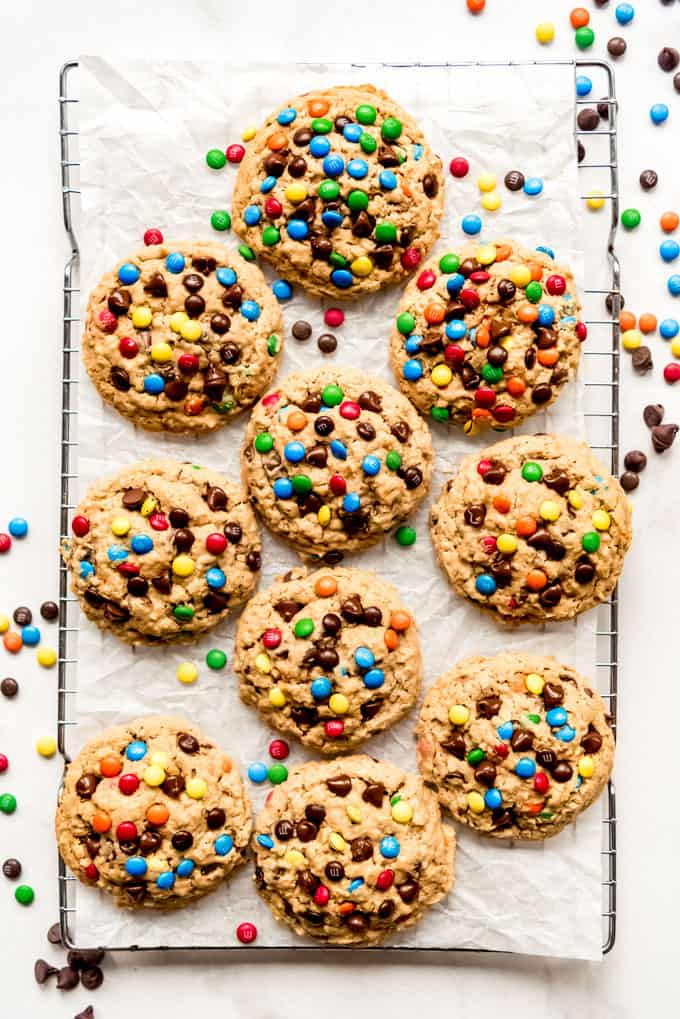 Large monster cookies on a wire rack with mini M&Ms.