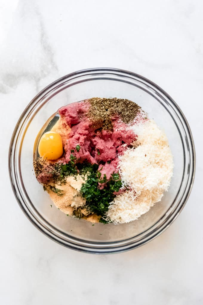 A glass bowl with meatball ingredients.