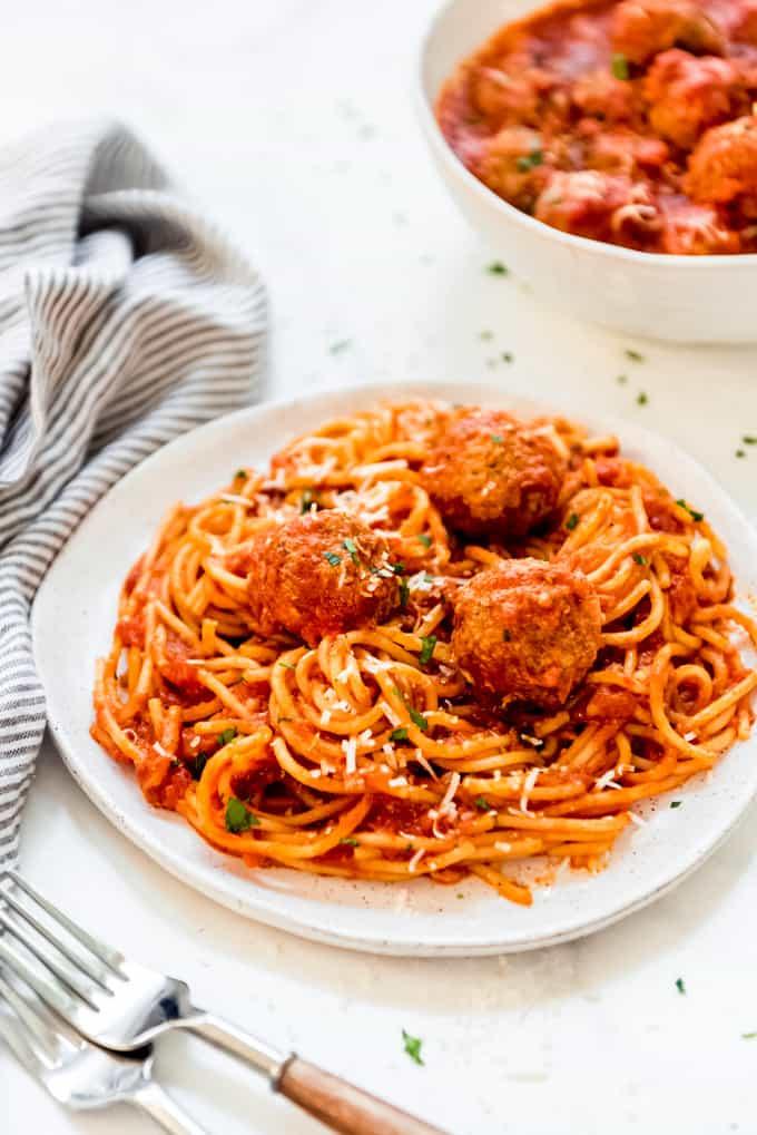 A plate of spaghetti and mozzarella stuffed meatballs with marinara sauce.