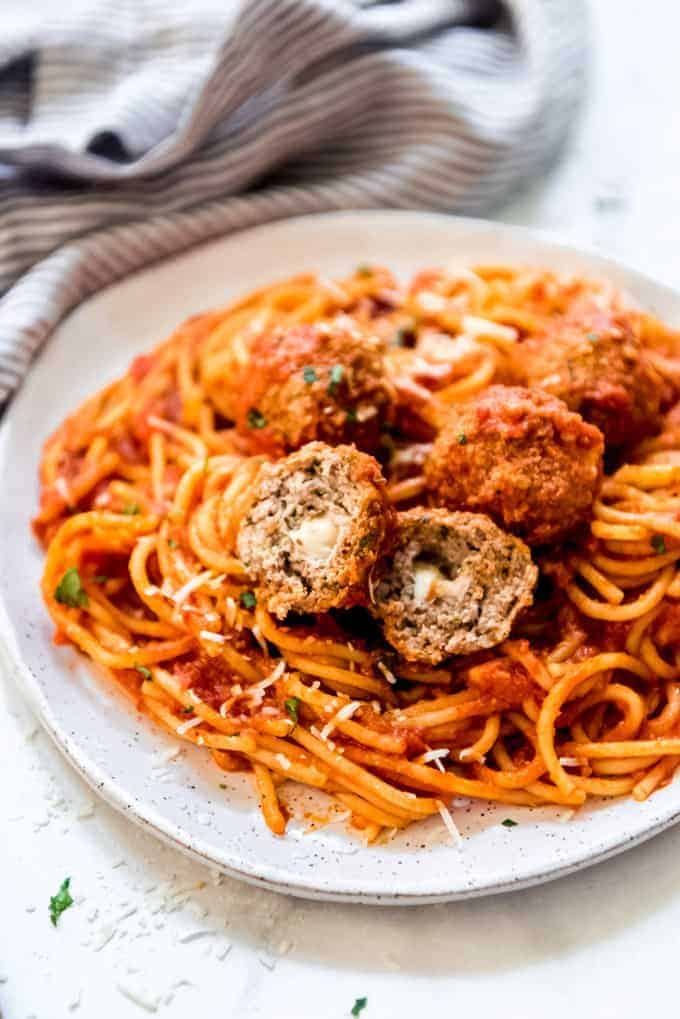 Mozzarella stuffed meatballs on a pile of spaghetti.
