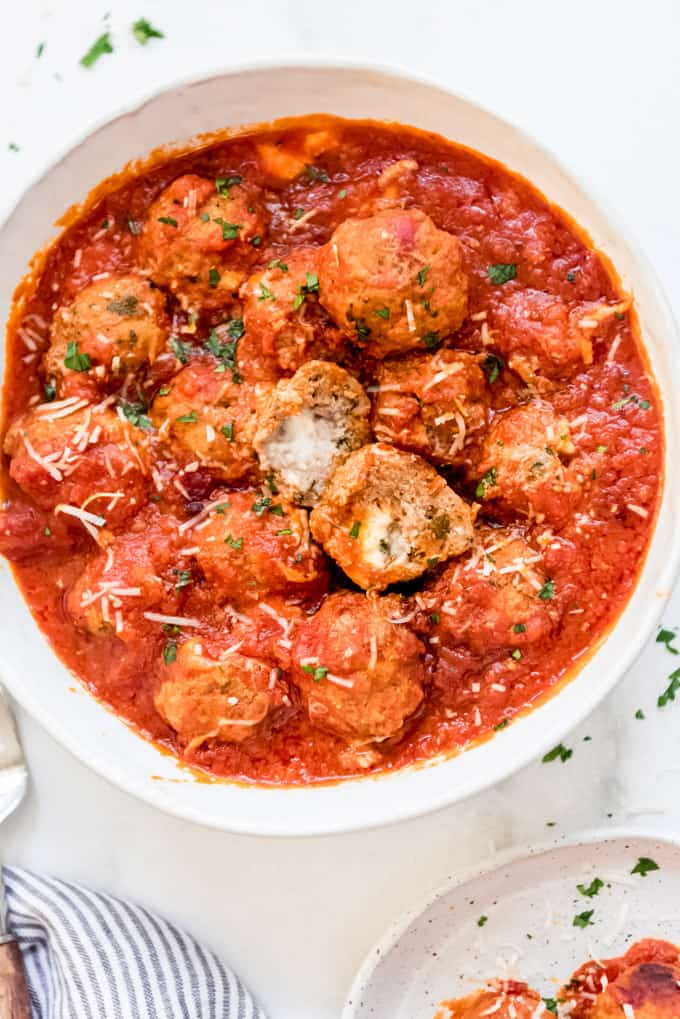 A large bowl of mozzarella stuffed meatballs in a tomato sauce.