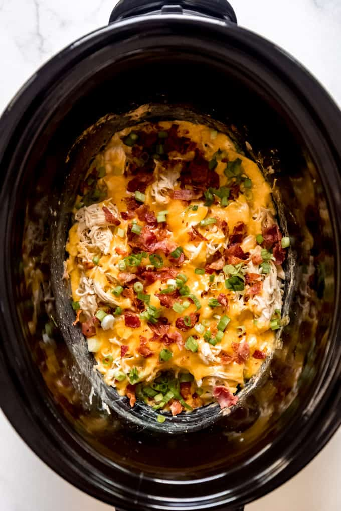 A slow cooker with shredded chicken covered in cheddar cheese, bacon, and green onions.