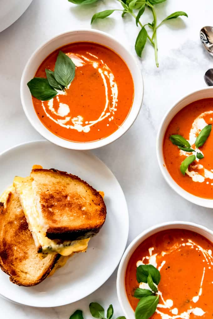 overhead shot of 3 tomato basil soup bowls drizzled with cream, beside fresh basil and grilled cheese