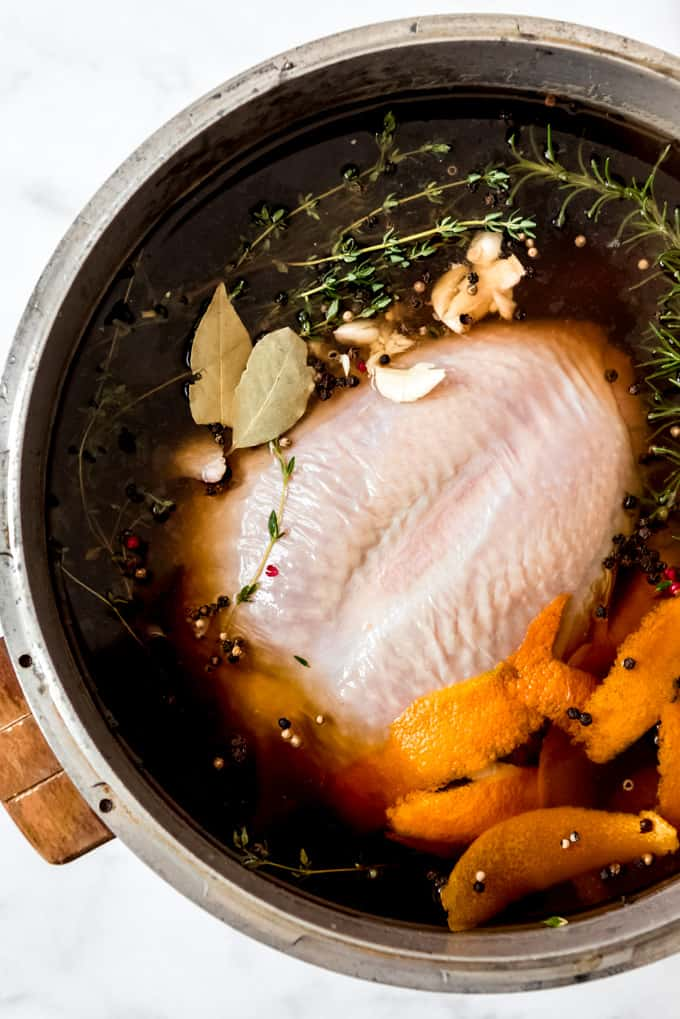 A turkey soaking in brine with herbs, orange peel, andn peppercorns.