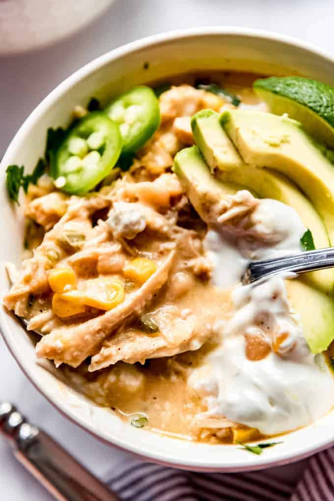 A bowl of white chicken chili with sour cream and avocado.