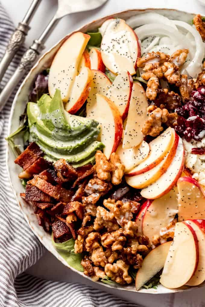 Apple salad with walnuts, bacon, avocado, cranberries, feta and poppyseed dressing in a bowl over a cloth.