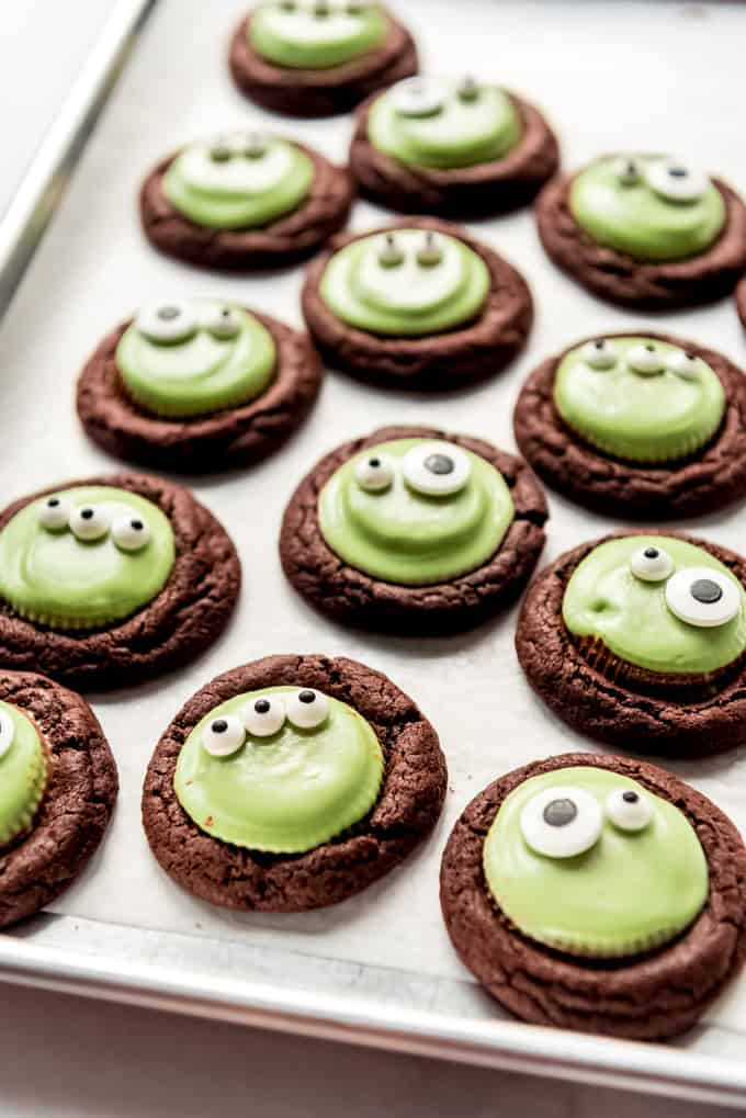 A dozen chocolate peanut butter cup monster cookies with googly eyes.