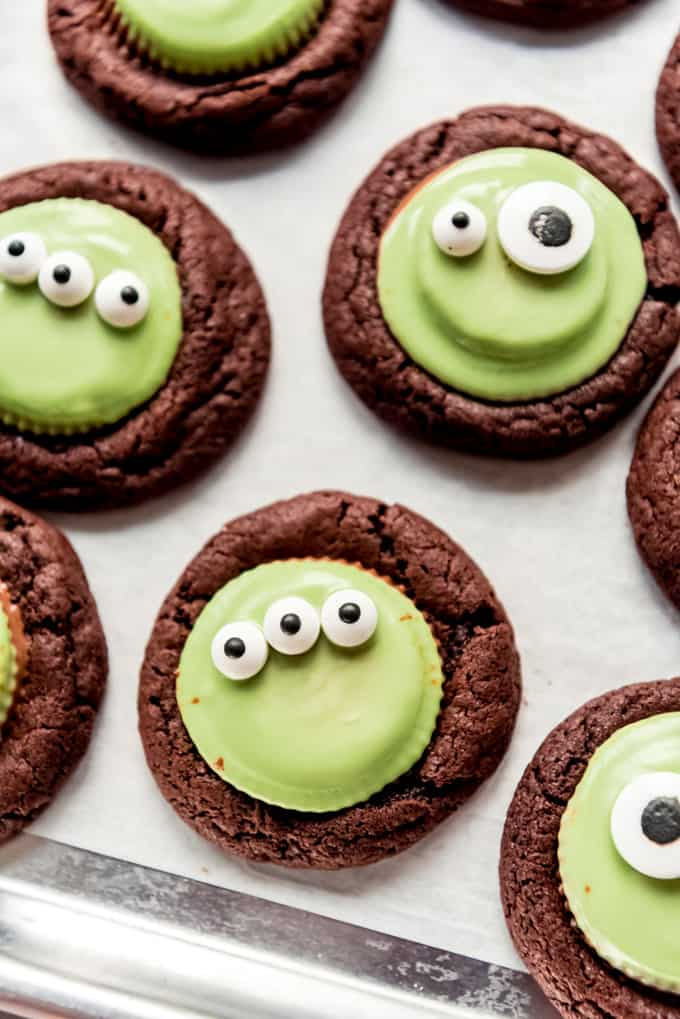 Chocolate cookies with melted green chocolate and candy eyeballs.