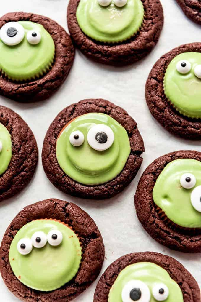 Chocolate cookies with green peanut butter cups and candy eyes on top.