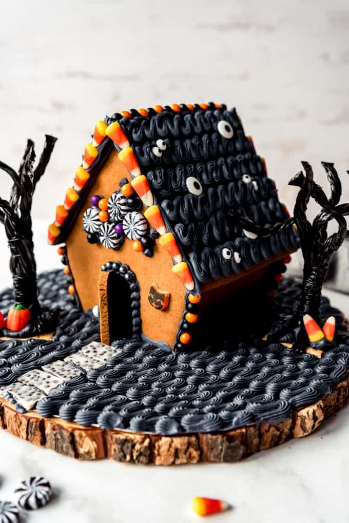 A gingerbread house decorated with black royal icing, candy, and licorice trees.