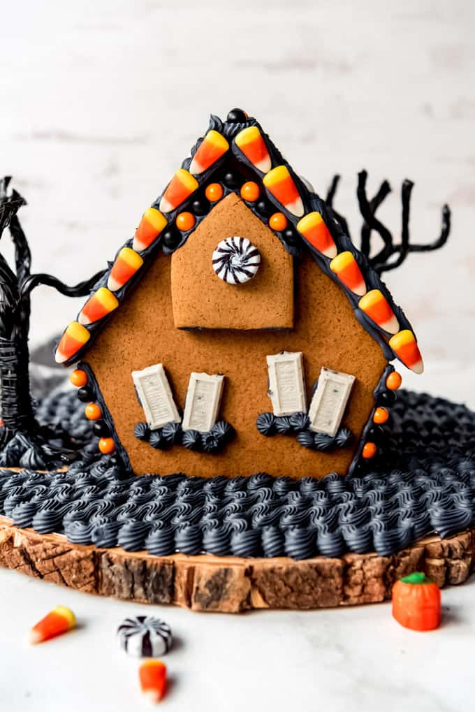 The back of a haunted gingerbread house decorated with candy corn and black royal icing.