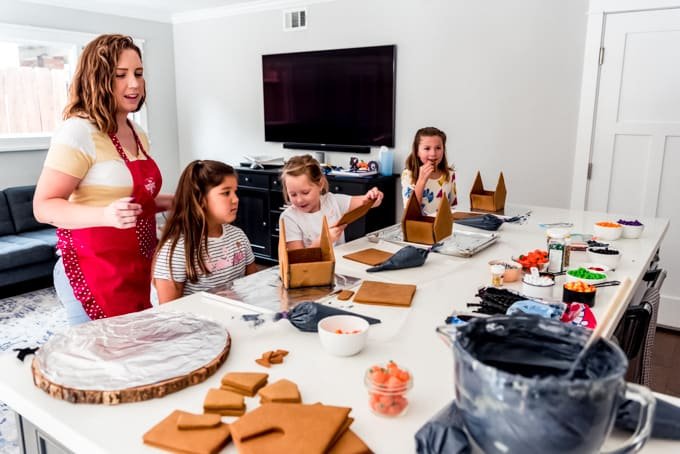 A mom and kids assembling gingerbread houses.