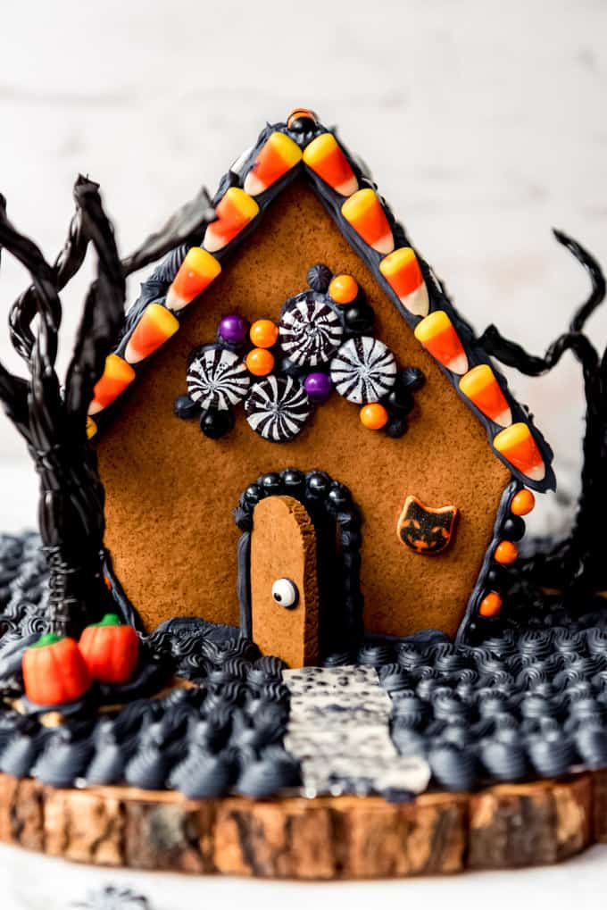 A homemade gingerbread house decorated for Halloween.