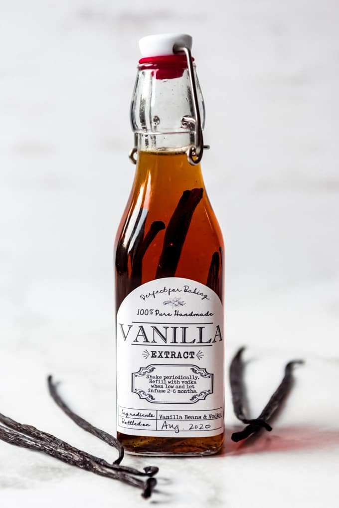 A bottle of homemade vanilla extract next to vanilla beans.
