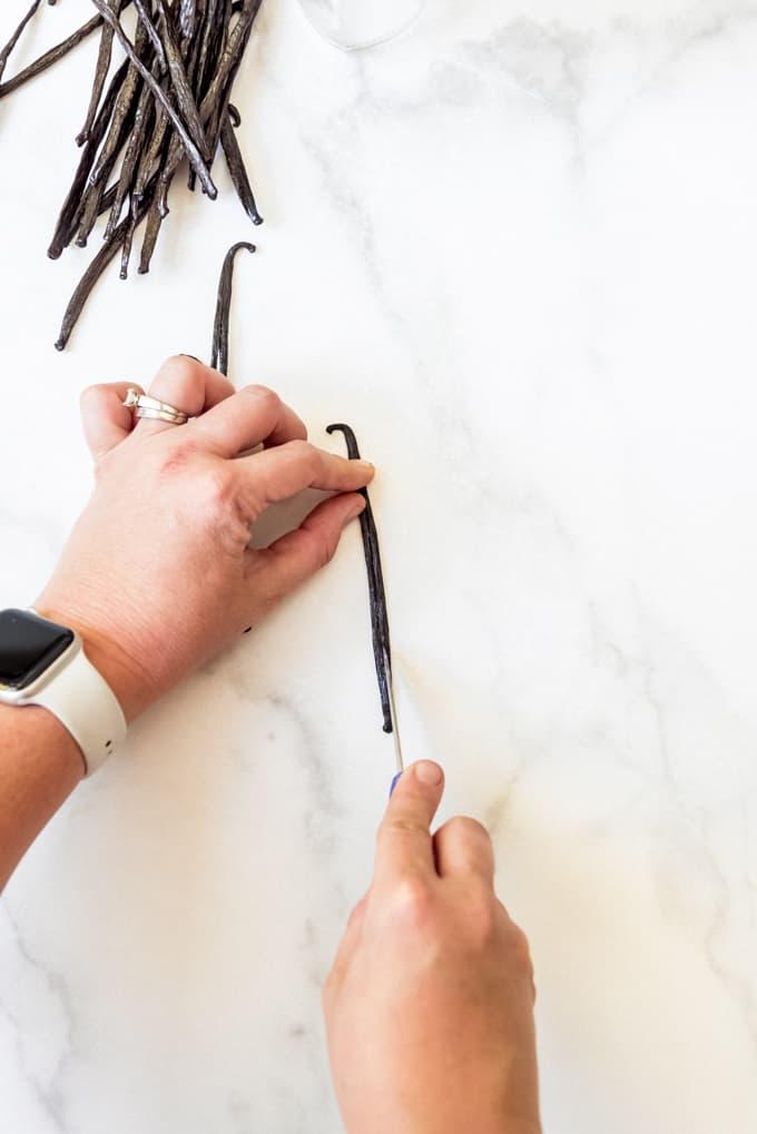 Splitting a vanilla bean open with a sharp knife.