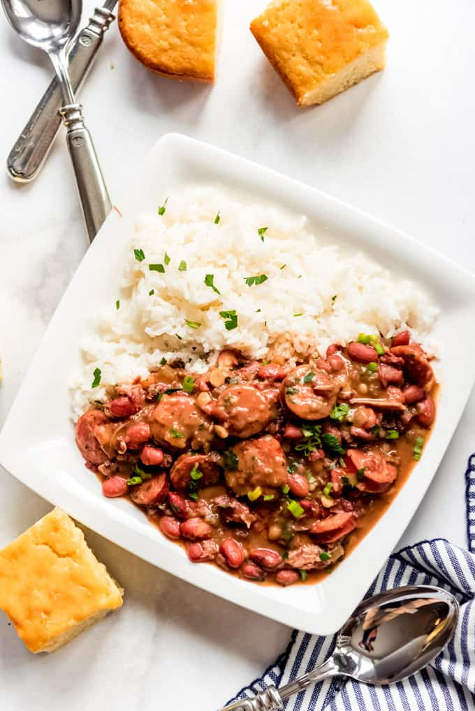 Square white plate of red beans and rice, with cornbread