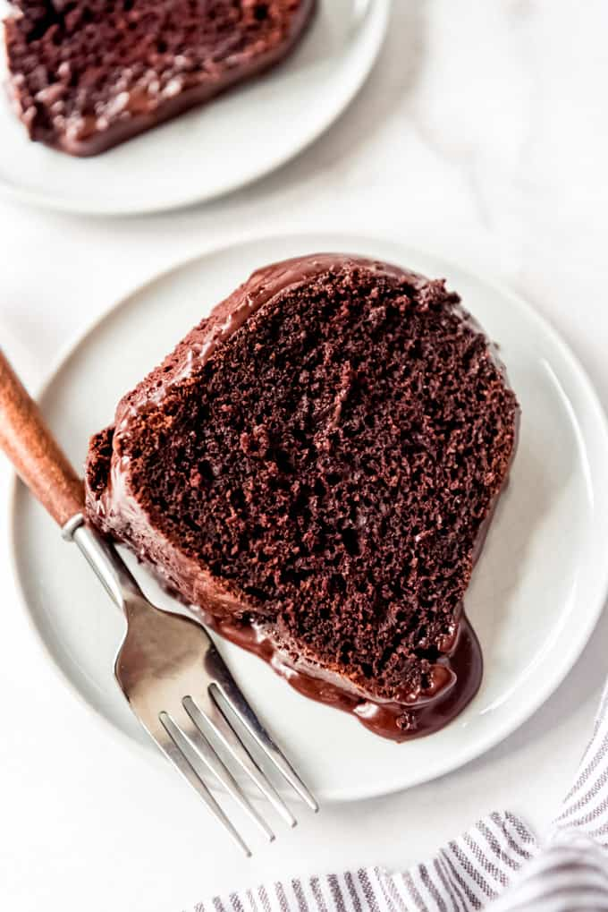 overhead, a slice of chocolate bundt cake on a white plate with a fork