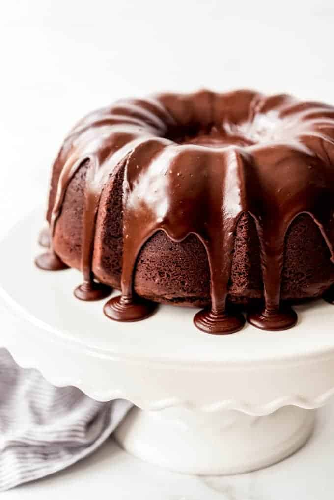 chocolate bundt cake on cake stand with icing pouring over sides