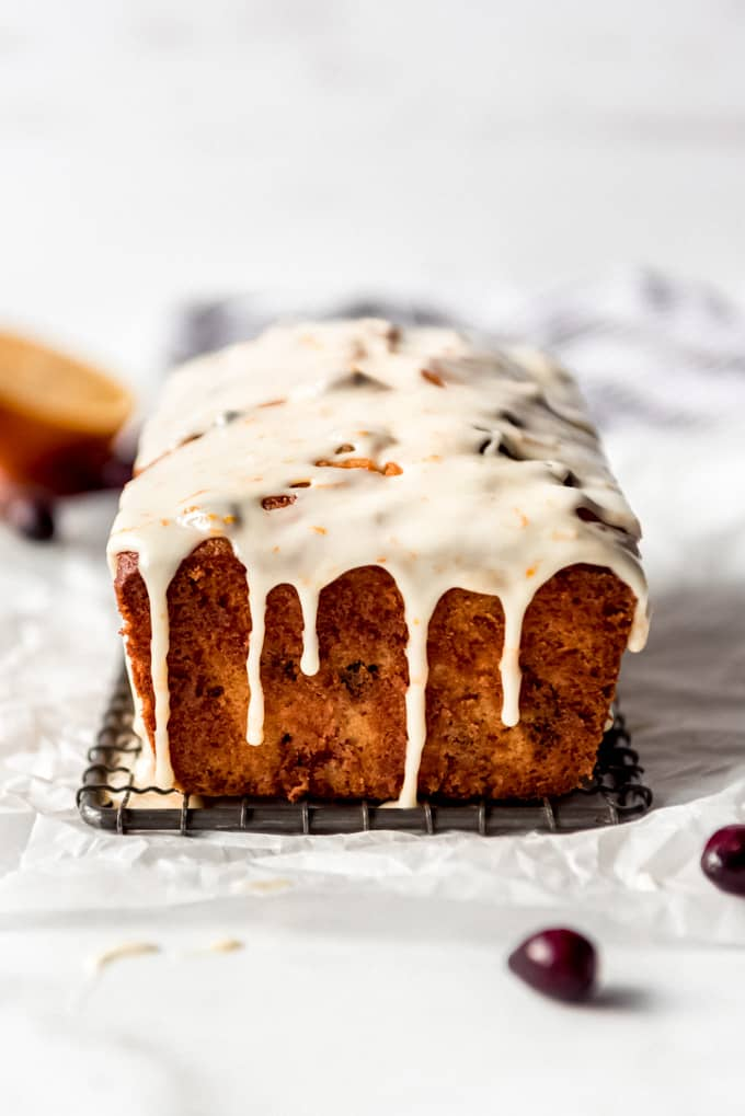 Orange glaze dripping down the sides of a loaf of cranberry orange bread.
