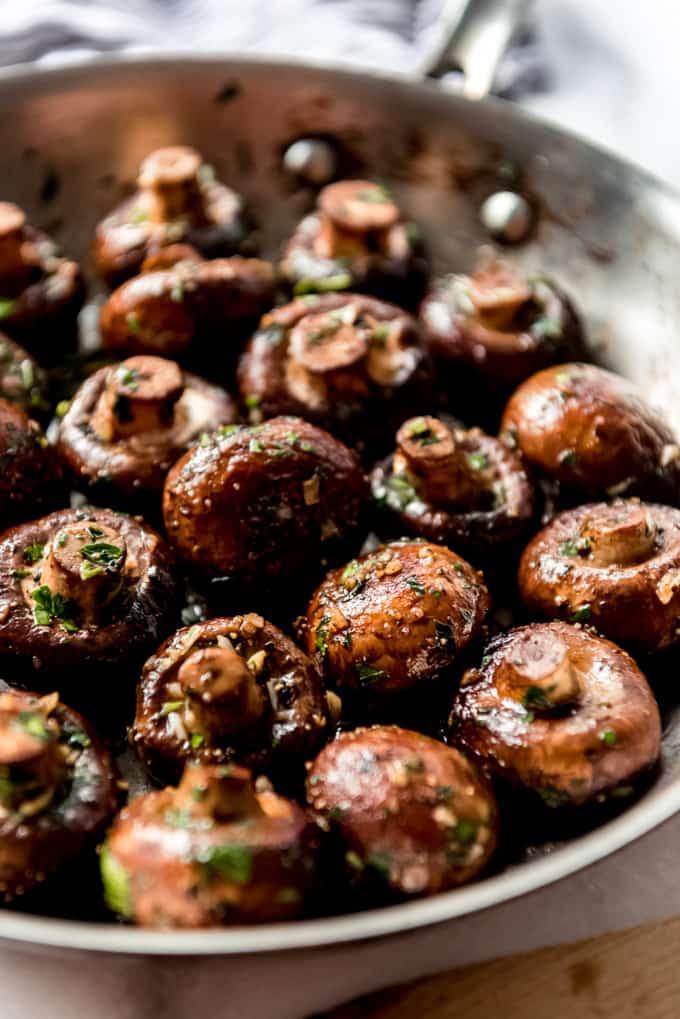 Cremini mushrooms in a pan with garlic and herbs.