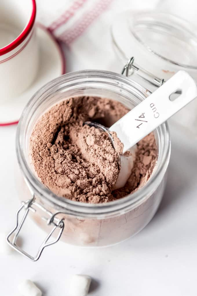 A measuring scoop in a jar of hot chocolate mix