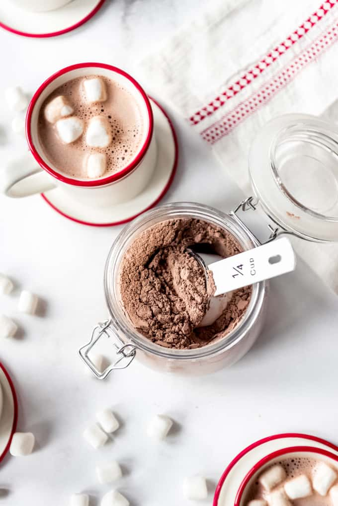 A cup of hot cocoa beside the powdered mix.