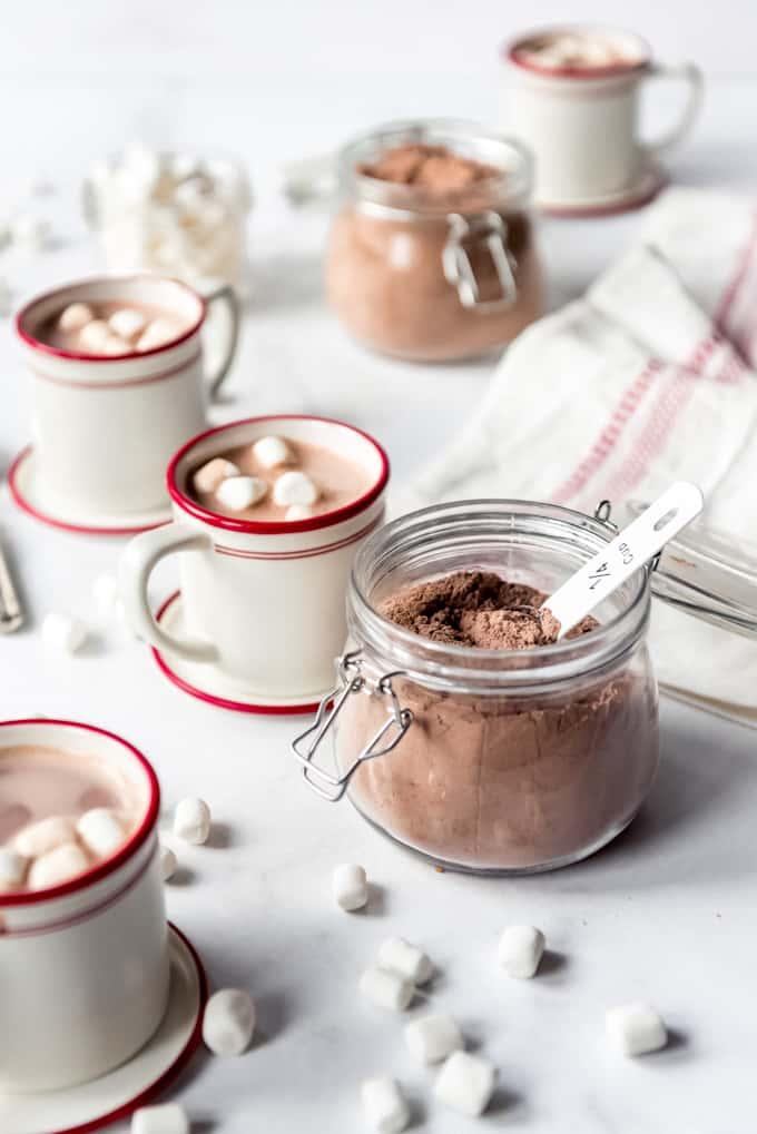 A jar of hot chocolate mix next to mugs of hot chocolate.